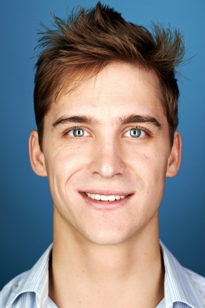 Portrait of real happy smiling man, natural on blue background