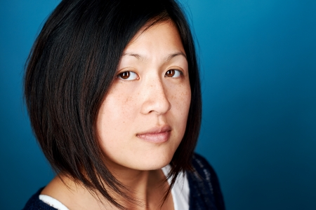 Portrait of real chinese woman on blue background Stock Photo - 22283381