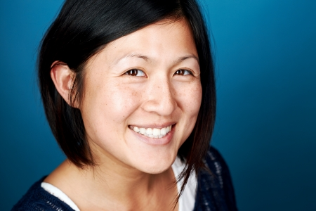 smiling portrait of real asian chinese woman happy on blue background Stock Photo - 22283382
