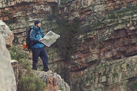 Man with map exploring wilderness on trekking adventure Stock Photo - 23032115