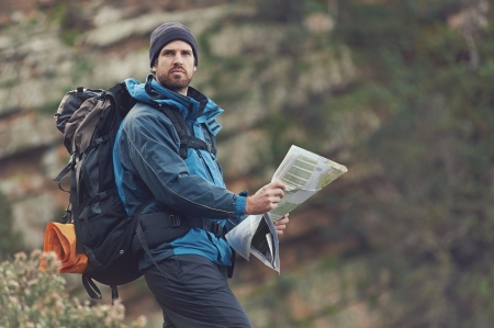 exlore: Portrait of man with map in wilderness mountains