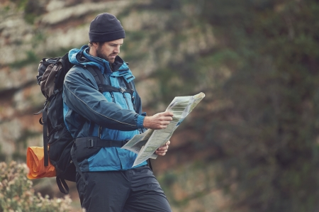 Man with map exploring wilderness on trekking adventure Stock Photo - 23032117