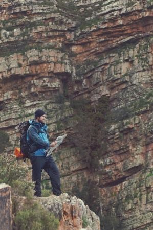 Man with map exploring wilderness on trekking adventure Stock Photo - 23032118