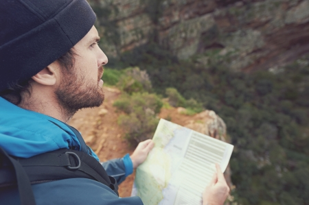 Man with map exploring wilderness on trekking adventure photo