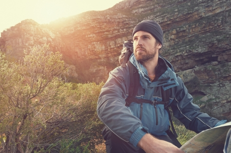 portrait of adventure man with map and extreme explorer gear on mountain with sunrise or sunset Banco de Imagens