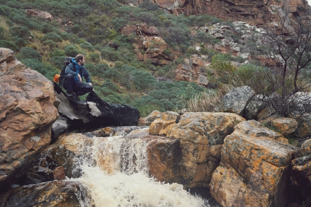 exlore: Adventure man crossing river on extreme hike in mountains alone