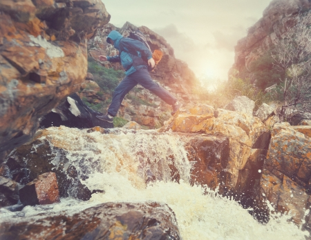 Survival man crossing river in mountains with backpack, sunrise or sunset and danger