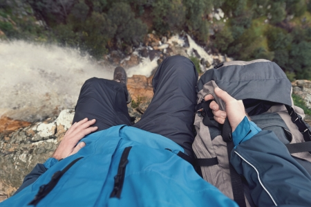 exlore: Man sitting on cliff edge looking at vie on outdoor lifestyle adventure hike