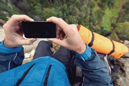 Adventure man with gps device or phone outdoors in wilderness exploring photo
