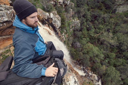 Man sitting on cliff edge looking at vie on outdoor lifestyle adventure hike Stock Photo - 22616465