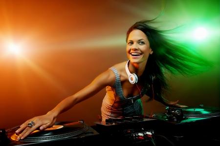 auriculares dj: Dj lindo de la mujer que se divierten tocando m�sica en la cubierta de disco de vinilo en el club fiesta vida nocturna Foto de archivo