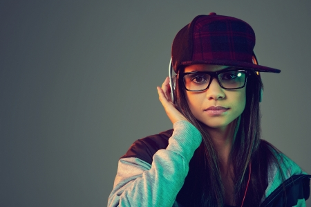 Portrait of trendy woman listening to music on headphones hiphop fashion photo