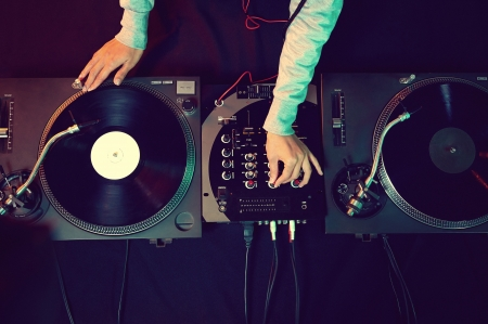 record: Dj hands on equipment deck and mixer with vinyl record at party