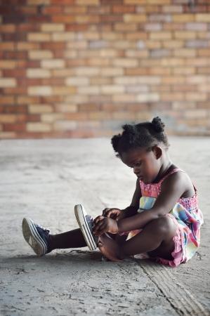 black tie: Muchacha africana joven que ata los cordones de los zapatos y poner rodaje a pie en el entorno rural