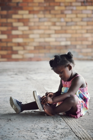 cute shoes: Young african girl tying shoelace and putting shoot on foot in rural setting