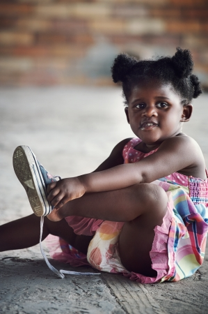 Junge afrikanische Mädchen binden Schnürsenkel und Putting shoot zu Fuß in ländlicher Umgebung