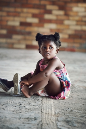 rural development: Young african girl tying shoelace and putting shoot on foot in rural setting