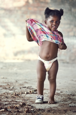 African poverty toddler with one shoe and diaper standing in rural area cute portrait photo