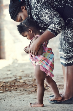 African mother teaching baby to walk in rural setting photo