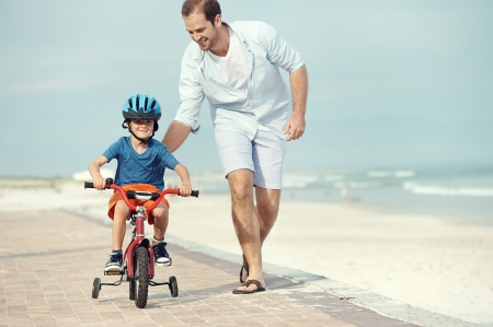 children running: Father and son learning to ride a bicycle at the beach having fun together