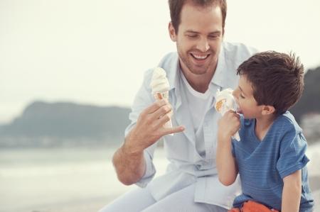 helados en cono: Padre e hijo comiendo helado juntos en la playa de vacaciones divirtiéndose con desorden de fusión