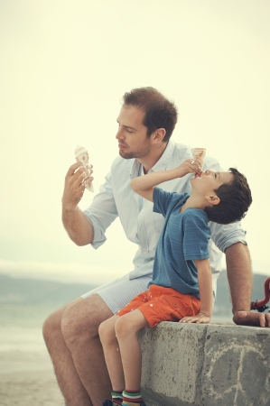 Father and son eating icecream together at the beach on vacation having fun with melting mess photo
