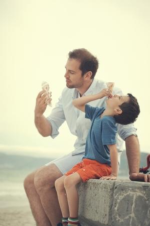 padre e hijo: Padre e hijo comiendo helado juntos en la playa en la diversi�n de vacaciones con desorden de fusi�n