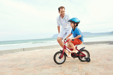children smiling: Father and son learning to ride a bicycle at the beach having fun together
