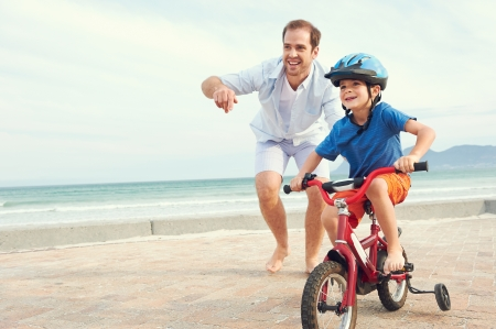 Father and son learning to ride a bicycle at the beach having fun together