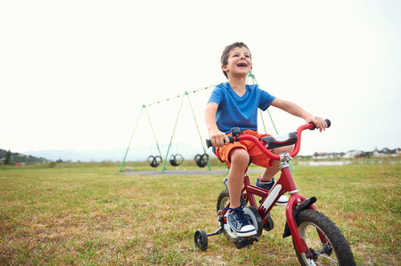 kids learning: Young boy learning to ride a bike with bicycle training wheels in park