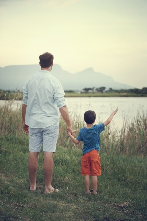hands out: Father and son holding hands looking out over the lake at the mountain at sunset Stock Photo