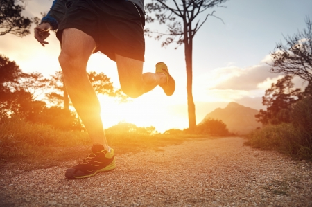 trail runner man exercising for fitness at sunrise in mountains doing sport photo