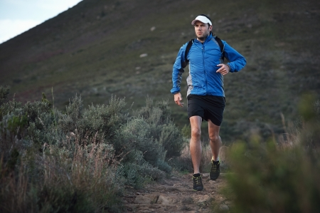 ultra: ultra marathon trail runner training in mountains for fitness and exercise wearing jacket