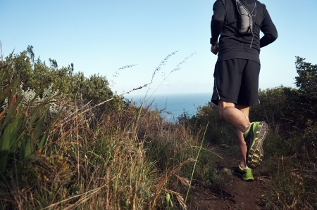 fitness running man on mountain trail near ocean exercising for marathon training photo