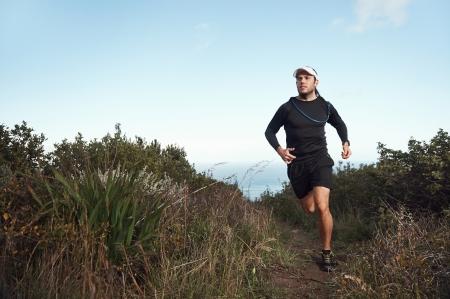 fitness running man on mountain trail near ocean exercising for marathon training photo
