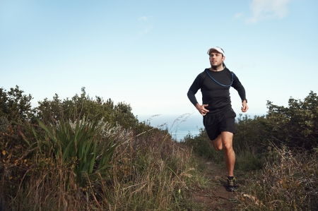 trail running: fitness running man on mountain trail near ocean exercising for marathon training Stock Photo