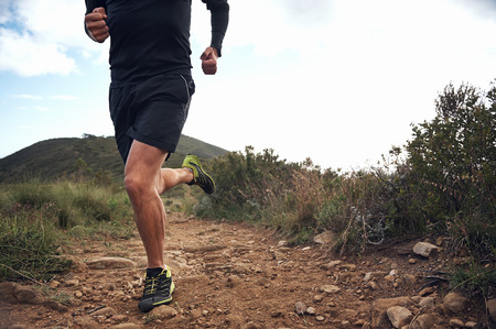 running race: trail running athlete exercising for fitness and health outdoors on mountain pathway