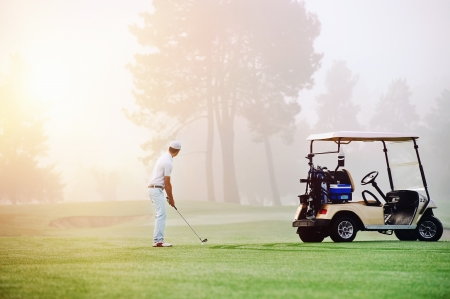 Golfer lining up shot with iron club on golf course in fairway at sunrise photo