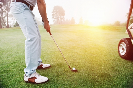 action shot: Golf approach shot with iron from fairway at sunrise Stock Photo