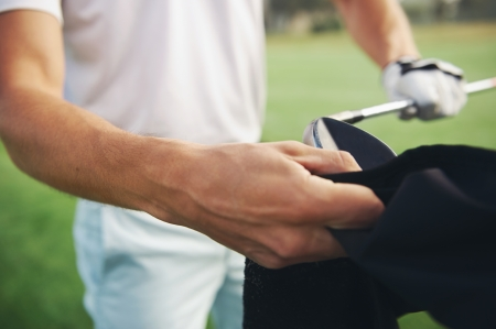 Golfer looking after his clubs by cleaning them after shot photo
