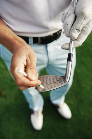 golf glove: golfer removes dirt and sand from grooves of iron club with a tee peg
