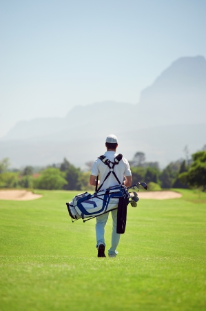 Golf player walking and carrying bag on course during summer game golfing photo