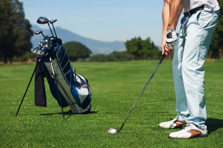 golfer man hitting golf ball from green fairway alone with bag on stand