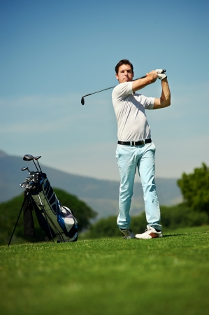 golfer man hitting golf ball from green fairway alone with bag on stand photo