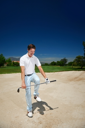 stuck: frustrated golfer in sand bunker on golf course loosing his temper Stock Photo