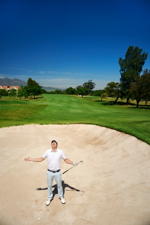 frustrated golfer in sand bunker on golf course loosing his temper photo