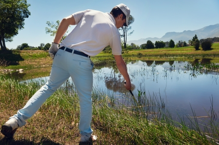 lost golf ball in water hazard golfer looking in reeds photo