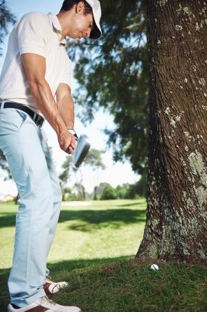 だいたい下手なショットの結果ツリーの背後にある困難な状況でゴルファー