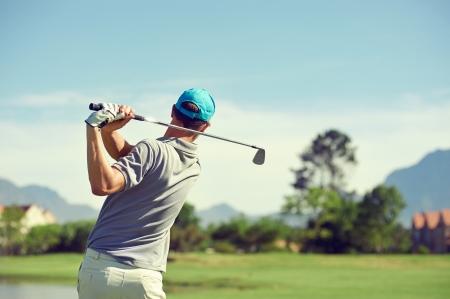 Golfspeler die golf geschoten met club op koers, terwijl op zomervakantie