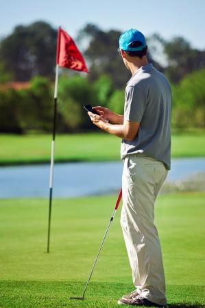 actores: golf hombre moderno con el tel�fono inteligente tomar puntuaci�n en el dispositivo gps m�vil junto al verde